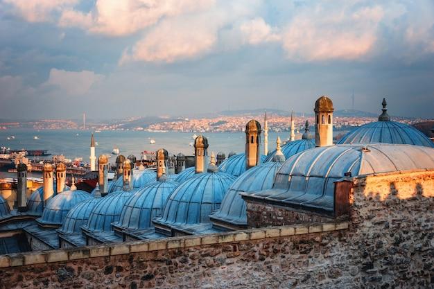 日没、イスタンブール、トルコのゴールデンホーンの美しい景色。イスタンブールの青い海に沈む夕日の光線でスレイマニエモスクの屋根