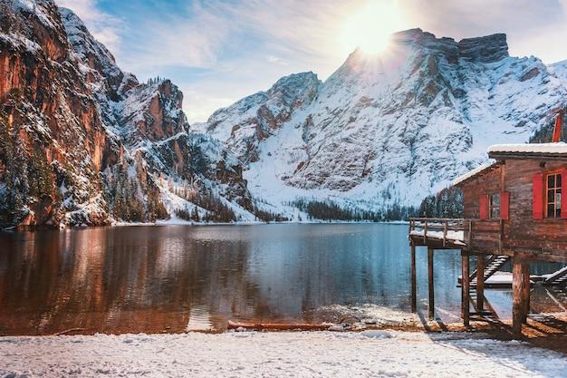 Деревянные дома в снегу на фоне кристально чистой воды озера браиес в доломитовых альпах, италия. красочный зимний пейзаж в заснеженных итальянских альпах, популярное туристическое место в италии