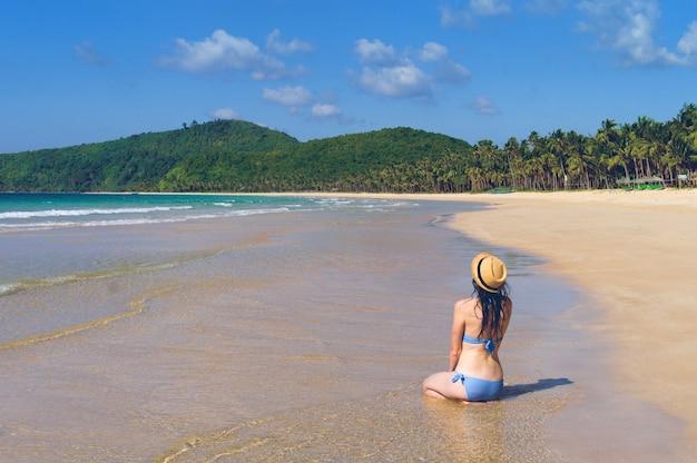 女の子は人けのないビーチに座っています。