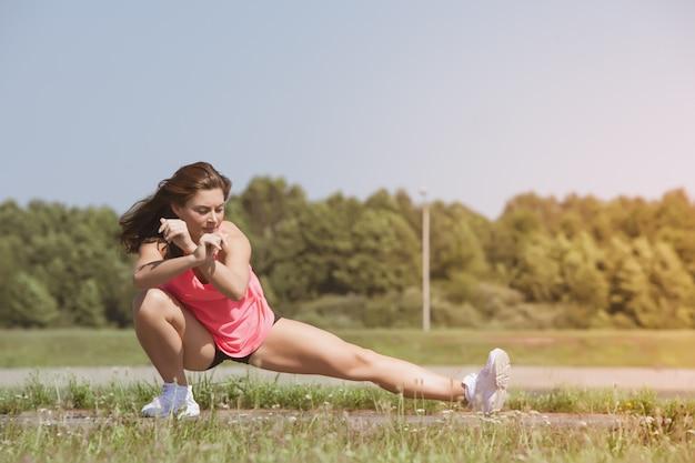 Молодая тощая девушка делая тренировку на траве.