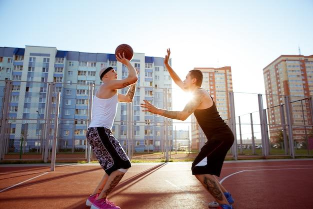 赤いコートでバスケットボールをする男