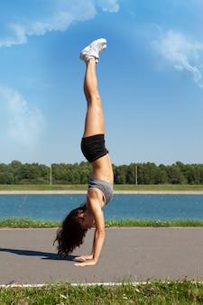 ヨガの頭をやっている若いスポーツ女性