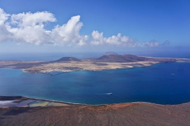 スペイン、カナリア諸島のランサローテ島の崖からラグラシオーザ島の眺め