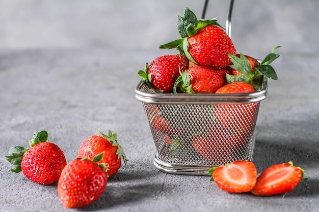 素朴な灰色の背景上のバスケットに新鮮なイチゴのヒープの写真。テーブルの上のスチールバスケットに熟したイチゴの束。コピースペース。健康的な新鮮な果物。自然食品。クリアフード