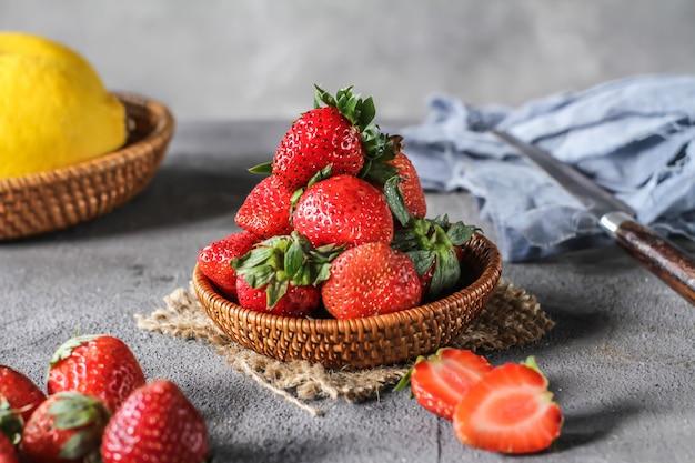 素朴な灰色の背景上にボウルに、新鮮なイチゴのヒープの写真。テーブルの上の木製のボウルに熟したイチゴの束。コピースペース。健康的な新鮮な果物。自然食品。木製かご