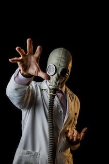 手で身振りで示す防毒マスクを持つ医師