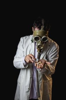 Доктор с противогазом принимает таблетки из бутылки
