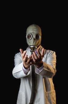 彼の手を示す防毒マスクを持つ医師