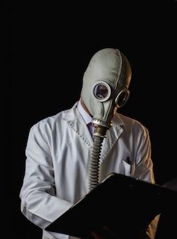 処方箋を書く防毒マスクを持つ医師