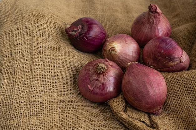 Лук с пурпурно-красной кожурой на джутовом коврике