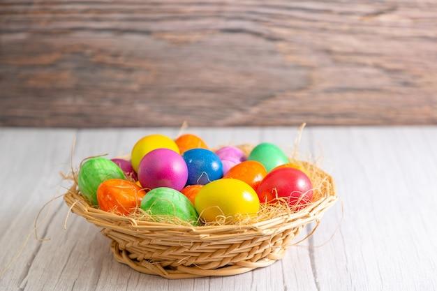 Красивая группа пасхальных яиц в весенний пасхальный день, красные яйца, синие, фиолетовые и желтые в деревянной корзине на столе фоне дерева