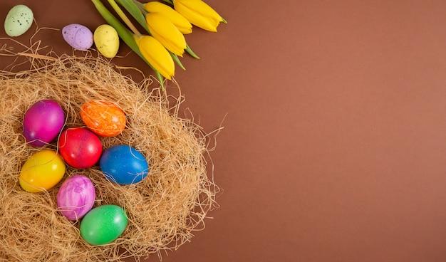 Красивая группа пасхальных яиц в весенний пасхальный день, красные яйца, синие, фиолетовые и желтые в деревянную корзину на коричневом фоне