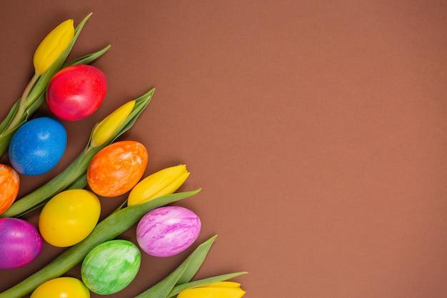 Красивая группа пасхальных яиц в весенний пасхальный день, красные яйца, синие, фиолетовые и желтые на коричневом фоне