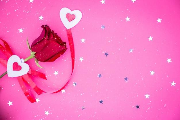 心と光沢のある星の紙吹雪と赤いバラ