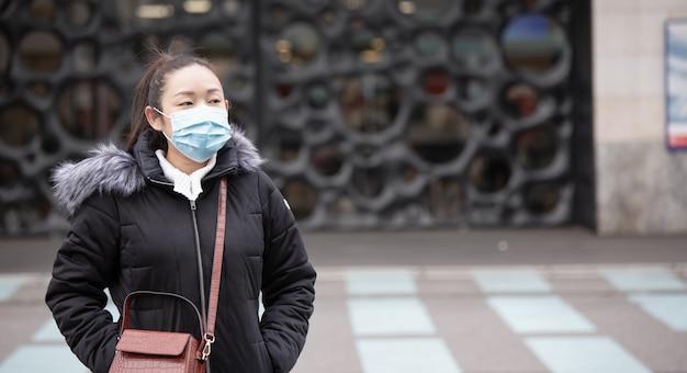 細菌、有毒ガス、ほこりを防ぐためにマスクを身に着けている若いアジア人女性の画像。