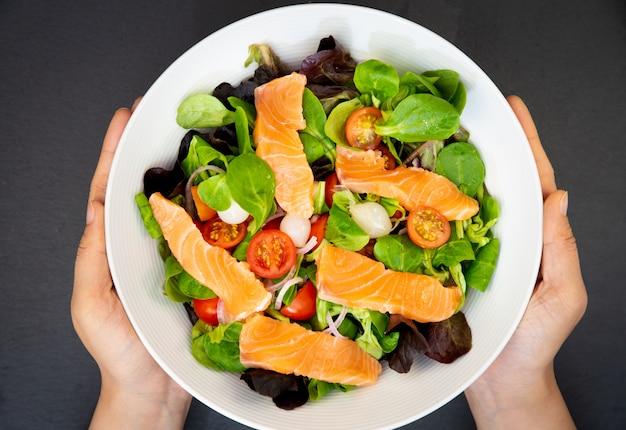 スイートトマト、ニンニクのピクルス、玉ねぎ、ほうれん草の新鮮なサーモンサラダは健康的な食事