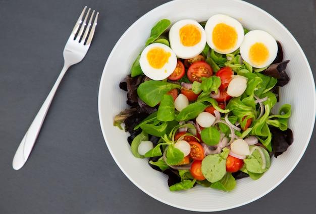 甘いトマト、ニンニクのピクルス、玉ねぎ、ほうれん草を混ぜたサラダエッグは、すべての食事の健康的な食事です。