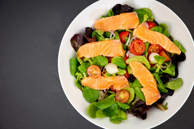 新鮮なサーモンのサラダ、甘いトマト、ニンニクのピクルス、玉ねぎ、ほうれん草は、すべての食事の健康的な食事です。