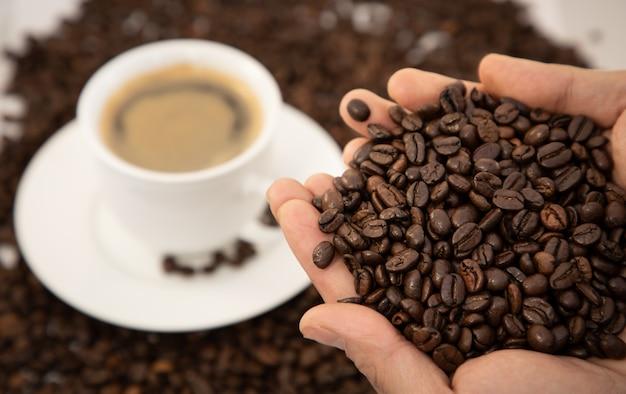 Конец-вверх кофейной чашки и фасолей на предпосылке деревянного стола.