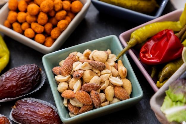 Миндальные орехи, арахис, специи, сладкий перец, тонг да тонг в маленькой чашке на красивом каменном подносе на столе
