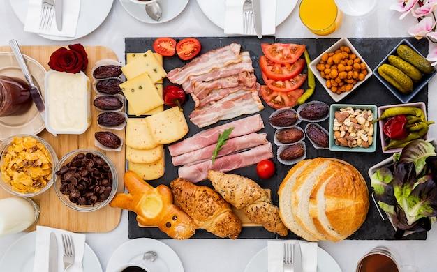 Завтрак на столе. хлеб с круассанами, круассаны, бекон, ветчина, сыр, салат, бобы, кукурузные хлопья, фрукты, кофе, чай и апельсиновый сок - это завтрак. , обед или ужин на каждый день