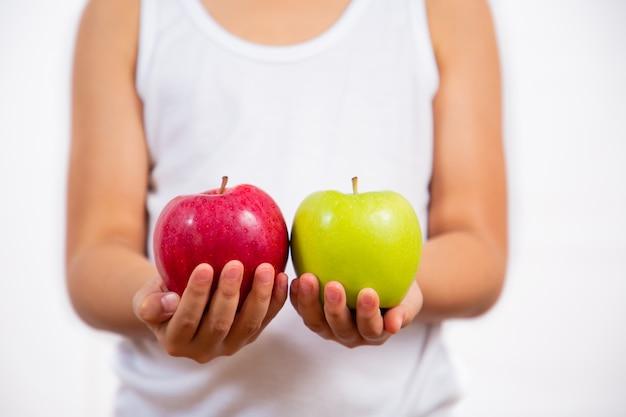 Фотография ребенка, держащего в руке красное и зеленое яблоко, здорова и хороша
