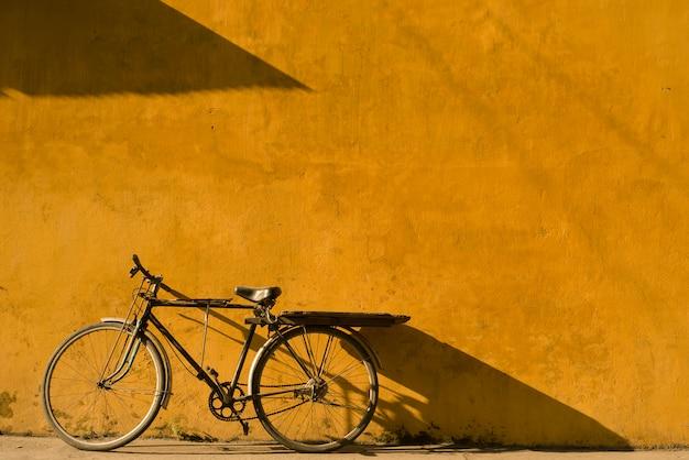ベトナムのホイアン市で黄色の壁にもたれて自転車