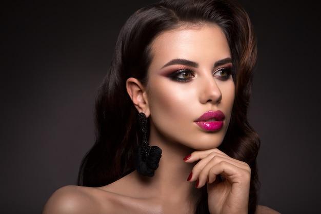 プロのメイクアップと美しい女性。ピンクの唇