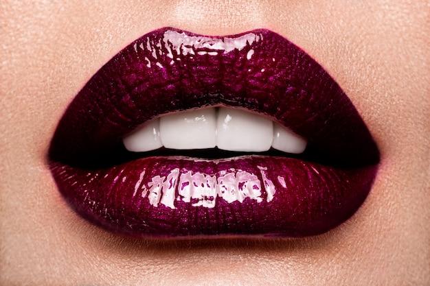 赤い光沢のある唇を持つ美しい女性をクローズアップ