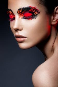 Красота фотомодели девушка с темно-ярко-оранжевым макияжем