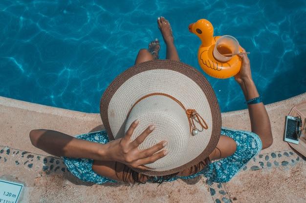 Женщина, сидящая на берегу бассейна с шляпой идеальный загар. туристический сайт на ривьере майя