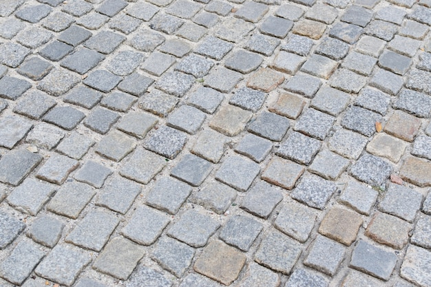 Серый старый каменный тротуар или гранитная булыжная дорога