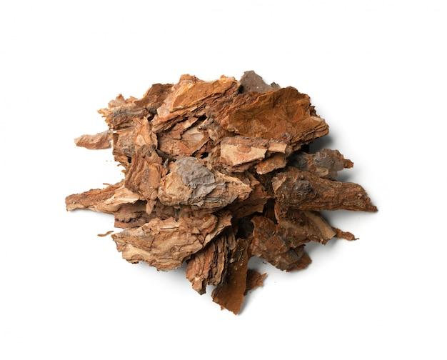白で隔離される乾燥した松の木の樹皮片のヒープ。壊れた森の自然チップ