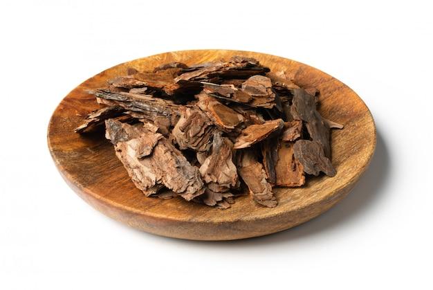 白で隔離される木の皿に乾燥した松の木の樹皮片のヒープ。ブロークンウッズネイチャーチップ