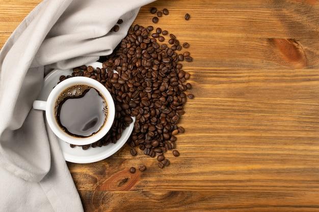 Чашка горячего эспрессо и кофейные зерна на коричневом взгляде сверху предпосылки деревянного стола.