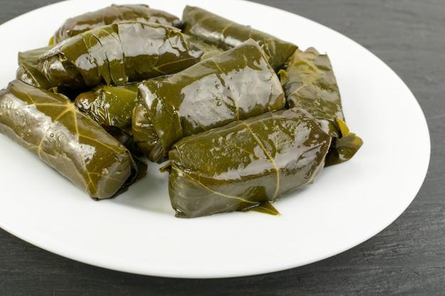 黒い石の背景に地中海料理ドルマダキアまたはトルマブドウの葉を詰めた