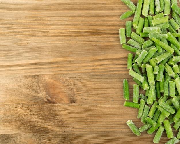 木材の背景にみじん切り冷凍インゲンのヒープ