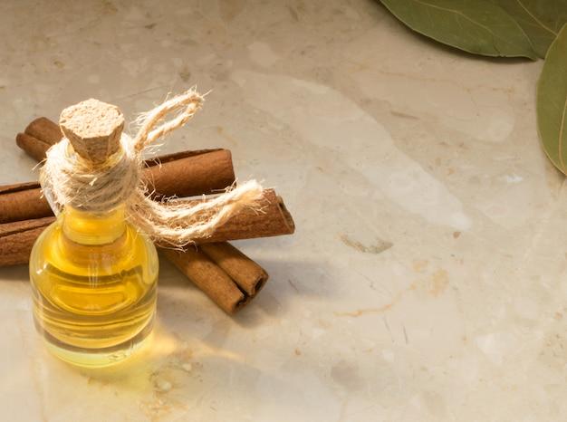 ベージュの大理石の背景に透明なガラス瓶の中のシナモンオイル。自然な日光のシナモンエッセンス