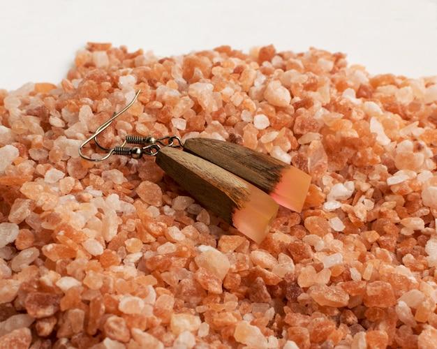 ピンクの塩の背景にジュエリーイヤリング。エポキシ樹脂と木材で作られた宝石