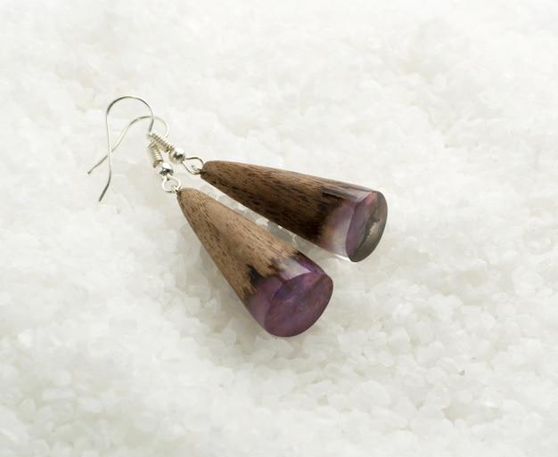 白いクリスタルの背景に手作りのイヤリング。エポキシ樹脂と木材で作られた宝石