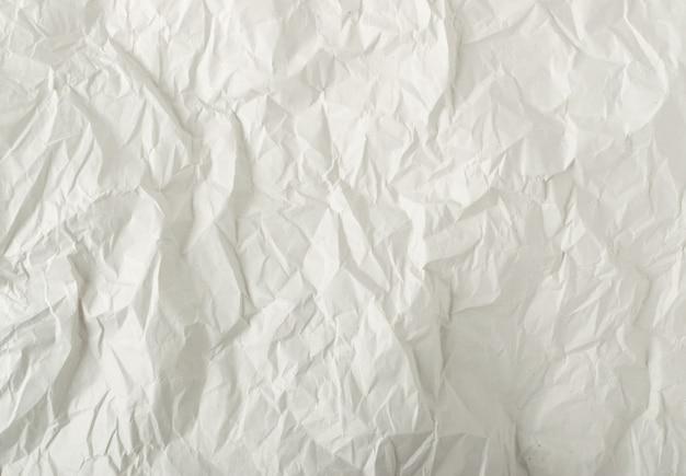 白い薄いしわくちゃのクラフトペーパーバックグラウンドトップビューのシート。しわ灰色の包装紙のテクスチャまたはパターン