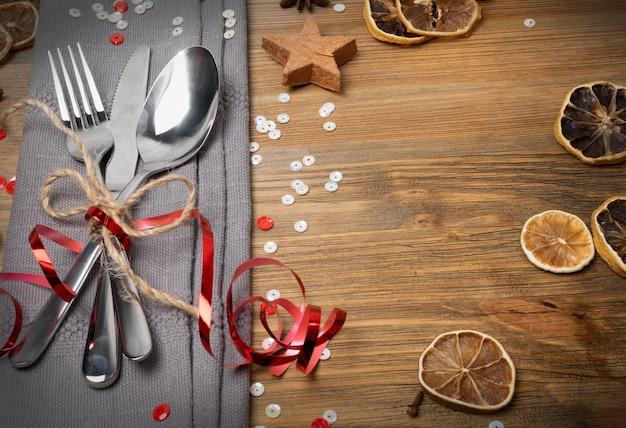 Сервировка стола рождественского обеда с столовыми приборами, серой салфеткой и видом сверху зимних специй.