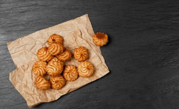 自然の焼きたてのココナッツクッキーまたは黒い石のテーブル背景にココナッツマカロン。茶色の羊皮紙の上面にココチップを搭載した自家製ダイエットビスケット