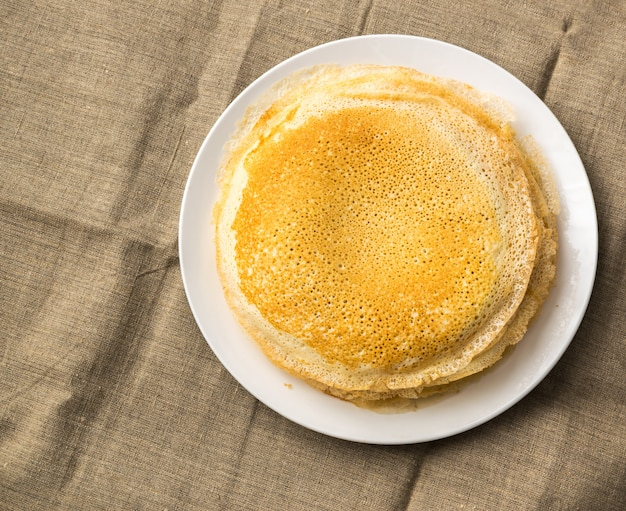 素朴な黄麻布の背景の上面に白い皿に薄いパンケーキのスタック。新鮮な自家製クレープフラットレイ