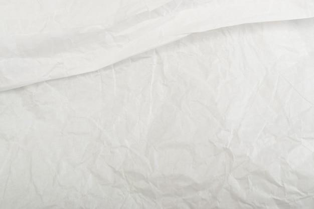 白い薄いしわくちゃのクラフトペーパーバックグラウンドトップビューのシート。