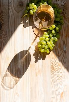 晴れた日にブドウの背景の熟した束の白ワインのグラス。木製の素朴なワイナリーテーブルトップビューで黄金のブドウのスパークリングドリンク付きワイングラス