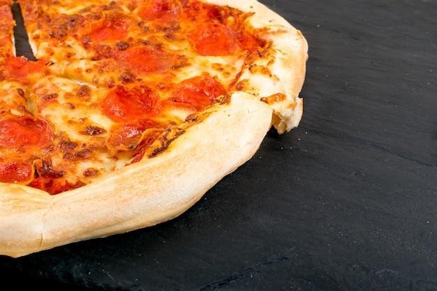Пицца пепперони или диабола с салями, перцем чили, сыром моцарелла, помидорами черри, томатным соусом на черном фоне крупным планом.