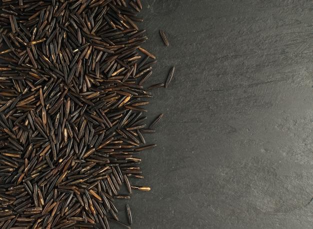 Сырой черный дикий рис текстуры фона