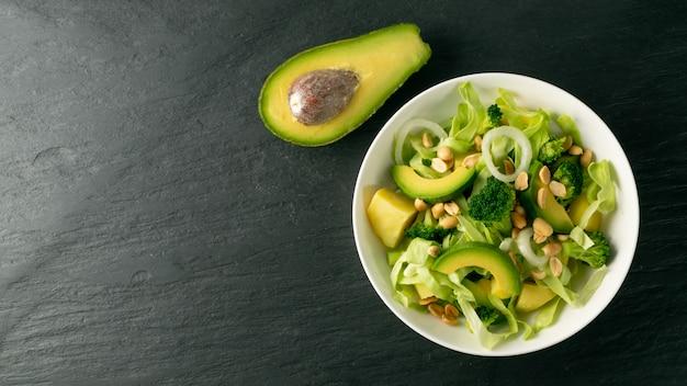Зеленый салат с авокадо, огурцом и орехами на белой тарелке