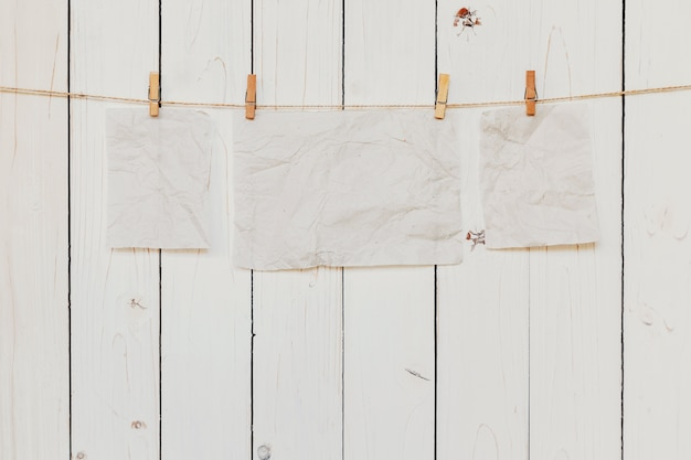 Пустая старая бумага, висит на фоне белого дерева с пространством для текста.